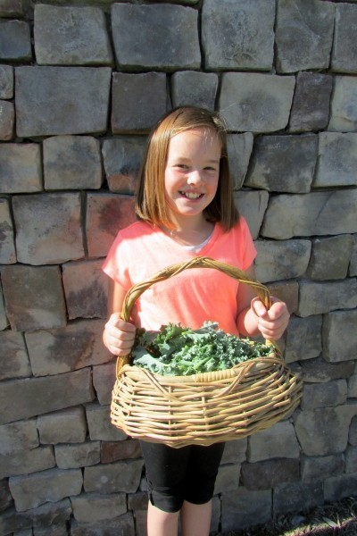 child with a basket of kale